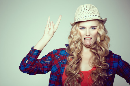 Young woman with camera. Blonde in a plaid shirt. Hipster fashion photographer girl. Young people, youth culture, open mouth tongue