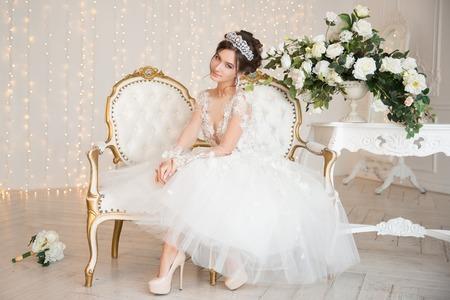 Die Braut in einem kurzen Kleid mit Spitze in der Krone Ohrringe.