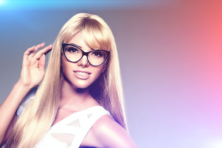 Beleza: Mulher nova da beleza com cabelo de luxo longo louro nos vidros.
