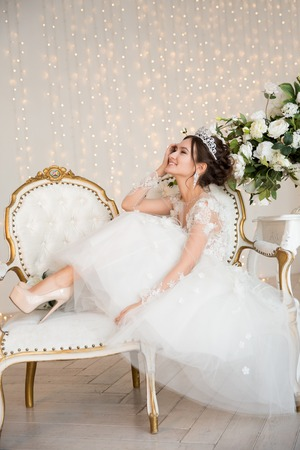 wedding dress: The bride in a short lace dress with the crown and earrings.