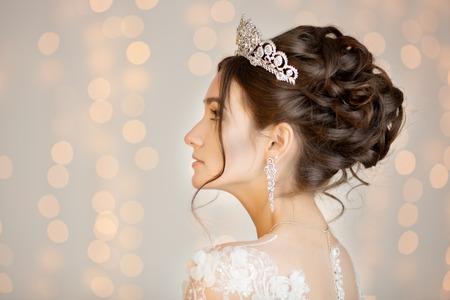 イヤリング、王冠とレースのドレスで花嫁。