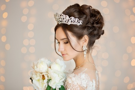 hair studio: The bride in a lace dress with the crown and earrings.