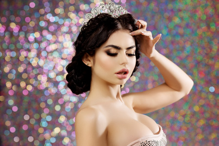 Woman in luxury dress and crown on lights party background Stock Photo