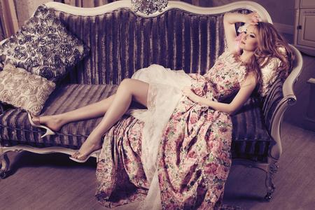 Stijlvolle vrouw in een vintage jurk in een luxuus inter