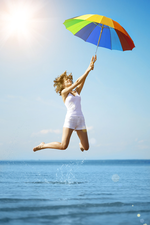 rainbow umbrella: Young woman jumping with rainbow umbrella on the beach.