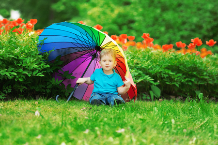 rainbow umbrella: baby with rainbow umbrella in park.