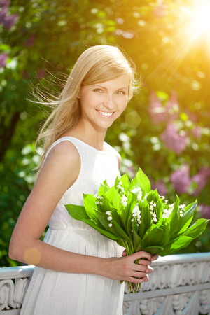 health woman: Young woman with a beautiful smile holding flowers.