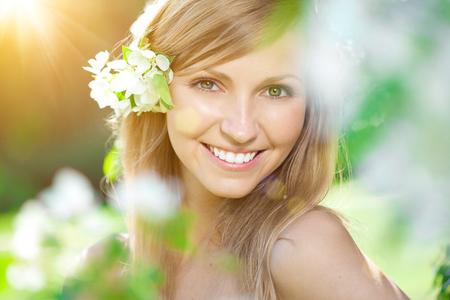 Mujer joven con una hermosa sonrisa con dientes sanos con flores.