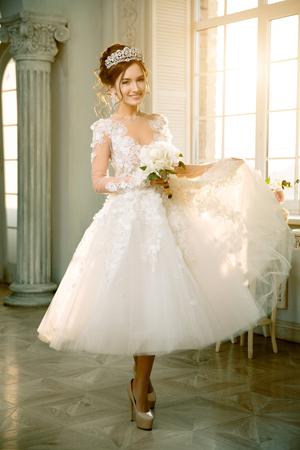 wedding dress: The bride in a lace dress with with the crown and earrings in luxurious interior.