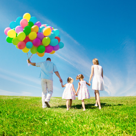 balloons: Happy family holding colorful balloons on a green  meadow. Stock Photo