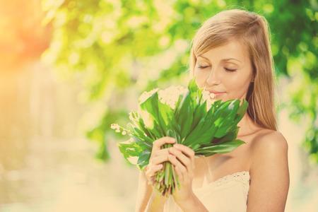 olfato: Retrato de una mujer joven oler las flores en un parque, al aire libre