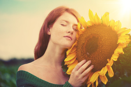 campo de flores: Hermosa mujer de pelo rojo con un girasol grande