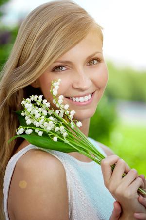 Jonge vrouw met een mooie glimlach met gezonde tanden met bloemen.