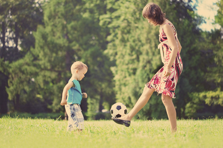 women playing soccer: mother and son playing ball in the park. Stock Photo