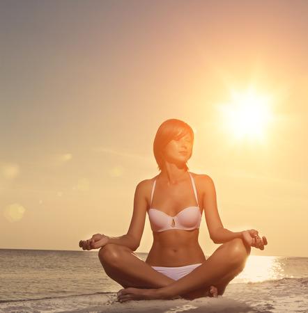 sun beach: a beautiful girl doing yoga on the beach at sunset Stock Photo