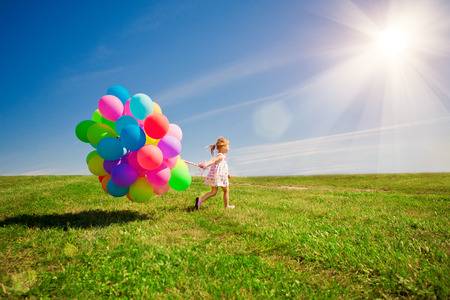Happy little girl holding colorful balloons on a green meadow.