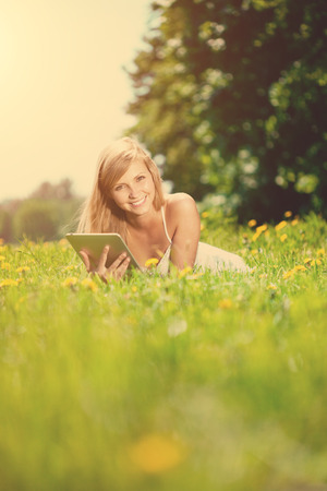 adult student: Portrait of young beautiful smiling woman with tablet pc, outdoors