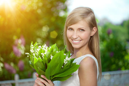 people laughing: Young woman with a beautiful smile with healthy teeth with flowers.