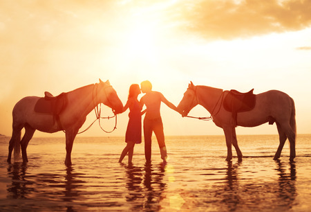 Loving couple kissing on the beach with Two horses at sunset Stock Photo