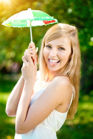 mini umbrella: Young woman with a beautiful smile with healthy teeth holding a mini umbrella