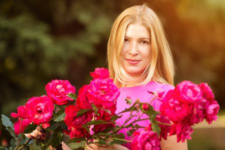 olfato: Mujer joven de moda de primavera con las rosas en el jardín de primavera.