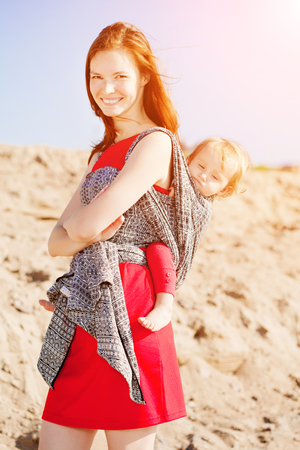 Beauty woman with a baby in a sling. Mom and baby. Mother and child. Stock Photo