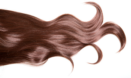 Luxury beautiful hair. A lock of curly voluminous healthy shiny hair on a white background.