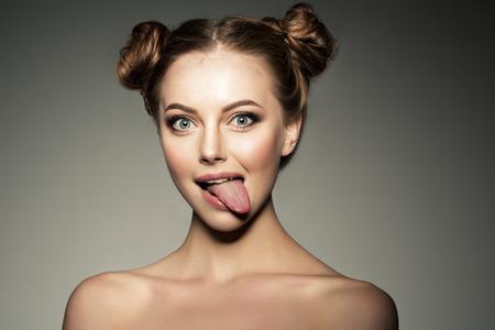 ragazza emotiva. Bella moderno modello di mostra la lingua Donna positiva pantaloni a vita bassa. Emozioni sul viso. Archivio Fotografico