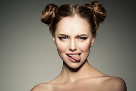 감정적 인 소녀. 아름 다운 현대 모델 혀를 보여줍니다. 긍정적 인 여자 hipster입니다. 얼굴에 감정.