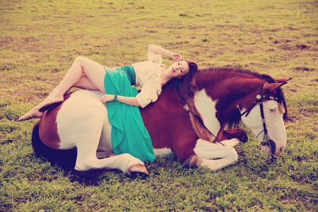 animal woman: Beautiful young woman with a horse in the field. Girl on a farm with animal. Luxury woman outdoors Stock Photo