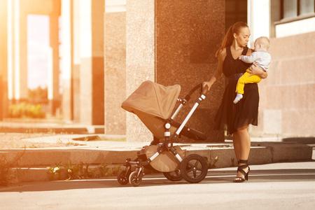Trendy moderne Mutter auf einer Stadtstraße mit einem Kinderwagen. Junge Mutter geht mit einem Kind in der Stadt. Schöne junge Frau mit einem Kind in einem Kinderwagen