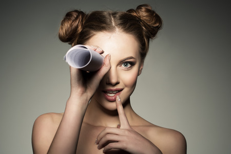 scouting: Scouting news and gossip. Beautiful girl looks in a telescope in the paper roll. Stock Photo