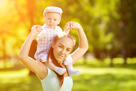 walk in: Cute little baby in summer  park with mother  on the grass. Sweet baby and mom  outdoors. Smiling emotional kid with mum on a walk. Smile of a child