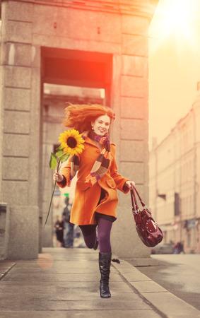 Schöne junge Frau in der Stadt. Mädchen auf einem Hintergrund städtischen Straßen. Stadt positiv und die Sonne. Standard-Bild
