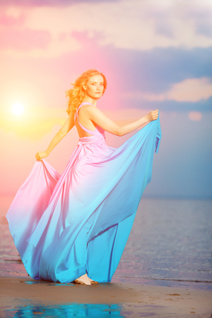 Luxury woman in a long blue evening  dress on the beach. Beautiful young girl at the sea. photo