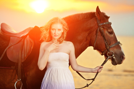 Beautiful woman riding a horse at sunset on the beach. Young beauty girl with a horse in the rays of the sun by the sea. photo