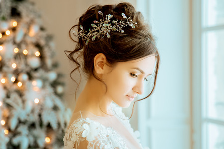 Braut. Hochzeit. Die Braut in einem kurzen Kleid mit Spitze in der Krone Ohrringe. Hochzeit Bouquet, Make-up, Frisur. Wedding Style Standard-Bild - 71077392