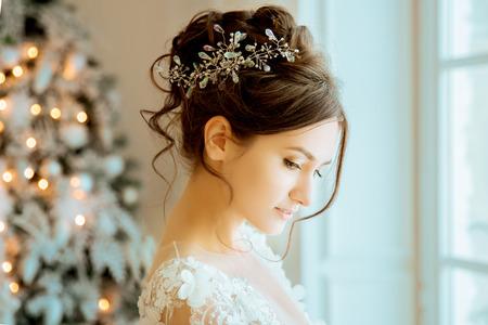 Brud. Bröllop. Bruden i en kort klänning med spets i kronans örhängen. Bröllop bukett, smink, frisyr. Bröllopsstil