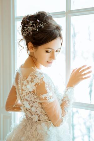 Braut. Hochzeit. Die Braut in einem kurzen Kleid mit Spitze in der Krone Ohrringe. Hochzeit Bouquet, Make-up, Frisur. Wedding Style Standard-Bild - 71077394