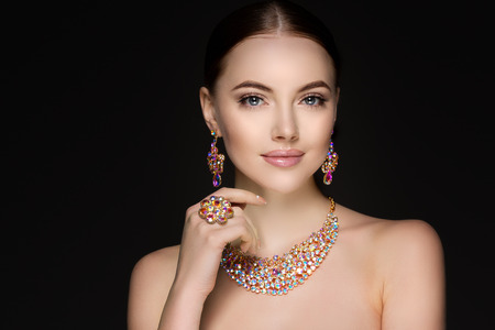 Beautiful woman in a necklace, earrings and ring. Model in jewelry from precious stones, diamonds. Фото со стока - 71621134