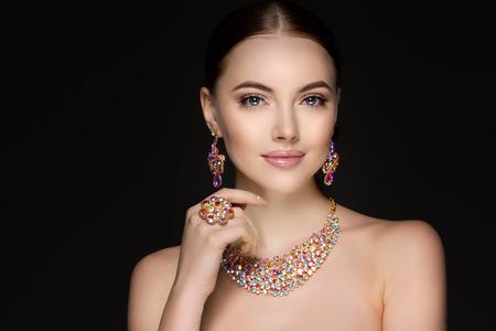 Mujer hermosa en un collar, aretes y anillo. Modelo en la joyería de piedras preciosas, diamantes.