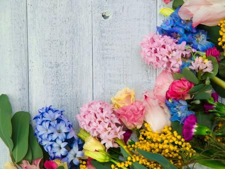 Flores da mola no fundo de madeira. Verão florescer fronteira sobre uma mesa de madeira. Imagens