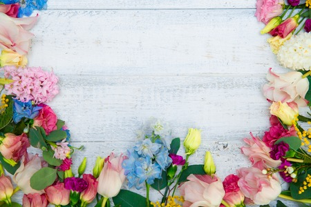 Spring flowers on wood background. Summer blooming border on a wooden table. Stock Photo - 72590463