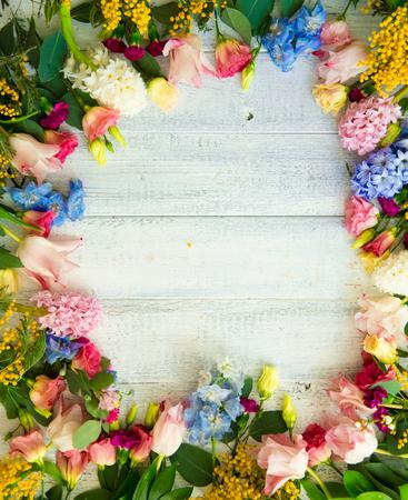 Wiosenne kwiaty na tle drewna. Lato kwitnących obramowanie na drewnianym stole.