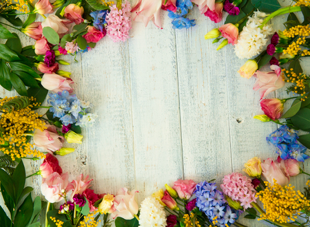 Spring flowers on wood background. Summer blooming border on a wooden table.