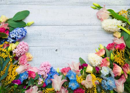 Wiosenne kwiaty na tle drewna. Lato kwitnących obramowanie na drewnianym stole. Zdjęcie Seryjne