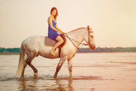 Woman and horse on the background of sky and water. Girl model on horseback on the beach by the sea at sunset, backlit in sunshine. A positive summer time scene. Stock Photo - 75748343