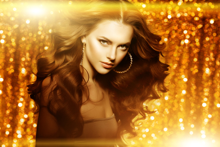 Golden beautiful fashion woman, model with shiny  healthy long volume hair. Waves curls updo volume hairstyle. Hair Salon.Girl with luxurious haircut on  gold background Banco de Imagens