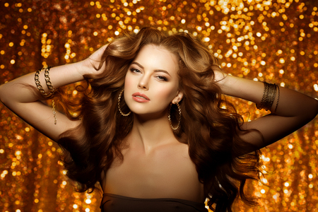 Golden beautiful fashion woman, model with shiny  healthy long volume hair. Waves curls updo volume hairstyle. Hair Salon.Girl with luxurious haircut on  gold background Stock Photo