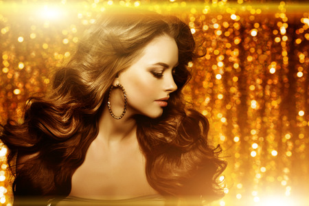 Golden beautiful fashion woman, model with shiny  healthy long volume hair. Waves curls updo volume hairstyle. Hair Salon.Girl with luxurious haircut on  gold background Archivio Fotografico